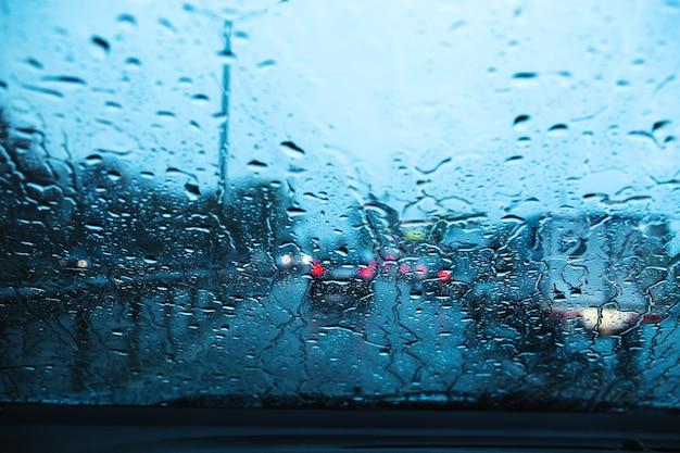 Stadtstraße durch windschutzscheibenautos abstrakter hintergrundwassertropfen auf den glaslichtern und -regen.