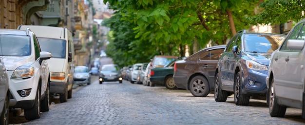 Stadtverkehr mit geparkten autos auf der straßenseite.