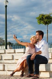 Städtetourismus - paare in den ferien auf einer bank