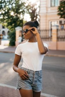 Städtische afroamerikanische frau, die auf dem stadtstraßenplatz auf sonnenuntergang geht