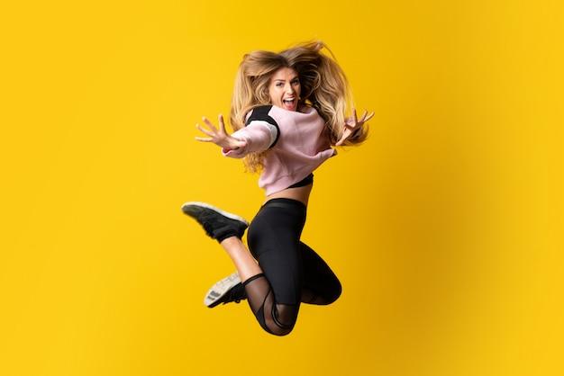 Städtische ballerina, die über lokalisierte gelbe wand und das springen tanzt
