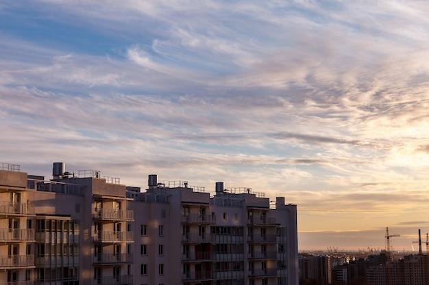 Städtische industrielandschaft am abend bei sonnenuntergang. schöner blauer himmel, kreative geschäftsgebäude und wohngebäude.