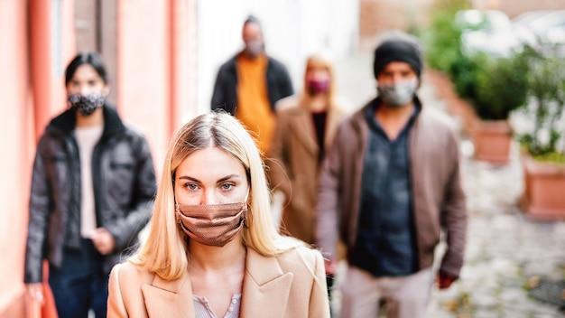 Städtische menge junger leute, die auf stadtstraße gehen, bedeckt durch gesichtsmaske