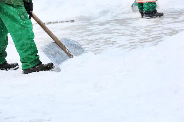 Städtischer arbeiter schneeräumung mit schaufel