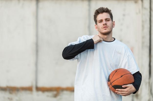 Städtischer basketballspieler des mittleren schusses, der die kamera gegenüberstellt