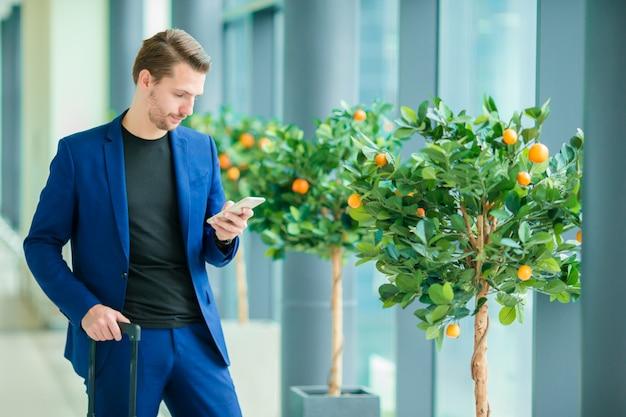Städtischer geschäftsmann, der nach innen am intelligenten telefon im flughafen spricht. tragende anzugsjacke des zufälligen jungen. kaukasischer mann mit mobiltelefon am flughafen beim warten auf einstieg