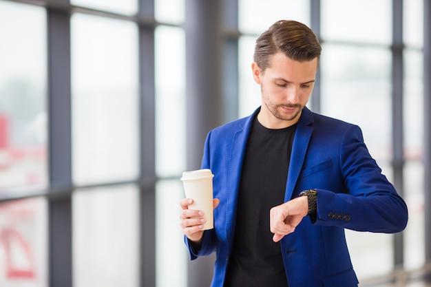 Städtischer mann mit kaffee nach innen im flughafen. ein junger mann kommt zu spät zum flug und schaut auf die uhr