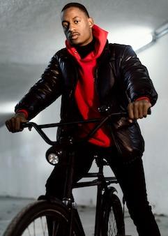 Städtischer radfahrer, der auf der niedrigen ansicht seines fahrrads sitzt