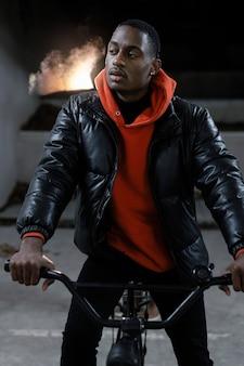 Städtischer radfahrer, der auf der vorderansicht seines fahrrads sitzt