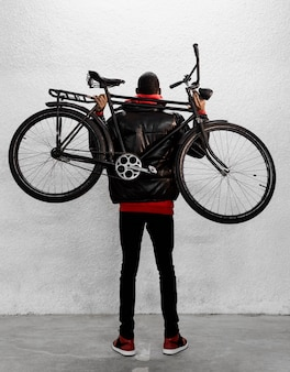 Städtischer radfahrer, der sein fahrrad hält
