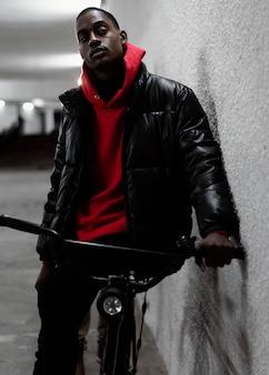 Städtischer radfahrer, der sich an eine wand lehnt