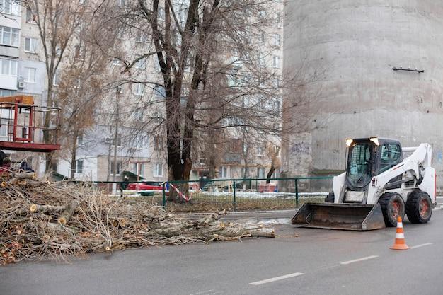 Städtischer rettungsdienst entfernt einen umgestürzten baum auf einer straße mit spezialausrüstung traktor.