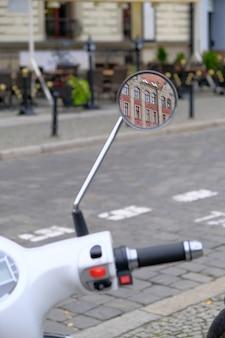 Städtischer weißer roller wird auf kopfsteinstraße in einem touristenzentrum der stadt geparkt