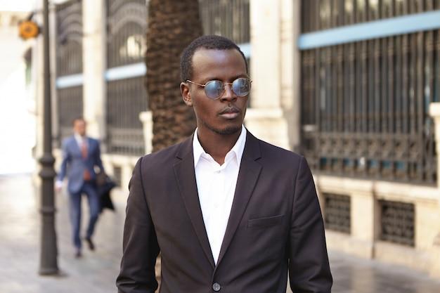 Städtisches außenporträt des selbstbewussten ernsthaften jungen dunkelhäutigen unternehmers, der stilvolle runde schatten und formellen anzug trägt, der auf straße gegen bürogebäude steht