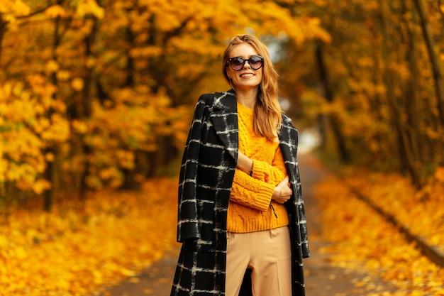 Städtisches junges frauenmodemodell im eleganten strohhut in der runden retrosonnenbrille im modischen gestreiften oberteil, das auf der sonne in der stadt aufwirft. sexy mädchen im stilvollen sommerkleid genießt das sonnenlicht im freien. trendige dame