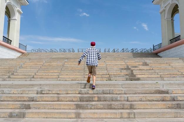 Städtisches konzept, junger mann, der auf der treppe in der stadt geht