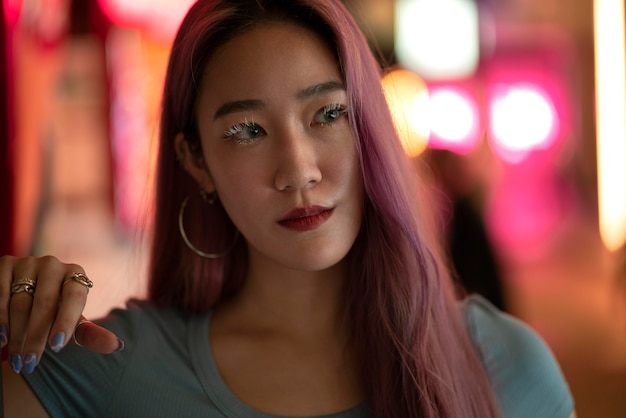 Städtisches porträt der jungen frau mit langen rosa haaren