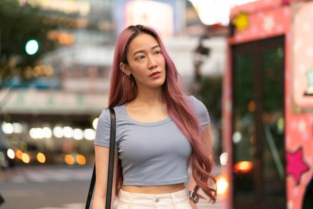 Städtisches porträt der jungen frau mit rosa haaren