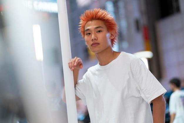 Städtisches porträt des jungen mannes mit orangefarbenem haar