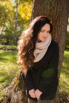 Städtisches porträt einer hübschen brünetten frau mit langen, gewellten haaren, die am sonnigen tag im park posiert