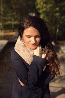 Städtisches porträt eines romantischen brünetten modells mit langem gewelltem haar, das rosa strickschal und blauen mantel trägt