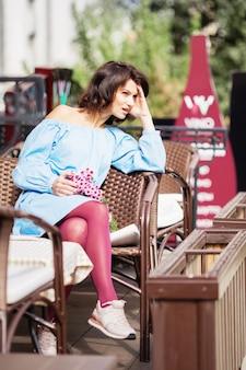 Städtisches romantisches porträt des schönen mädchens, das hellblaues kleid und burgunderfarbene strumpfhosen trägt