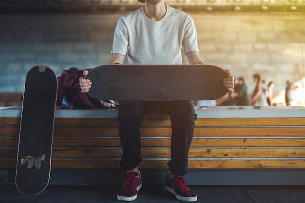 Städtisches straßenporträt des jungen hippies sitzen auf der bank mit skateboard outdoo.rs
