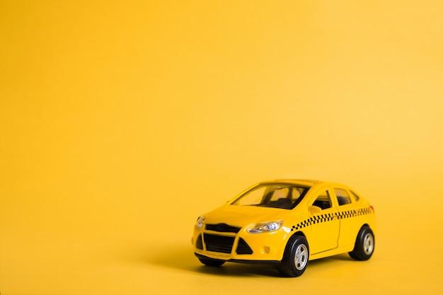 Städtisches taxi und lieferservice-konzept. spielzeug gelbes taxi-automodell