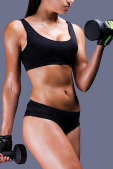 Stärkung ihrer muskeln. nahaufnahme einer jungen sportlichen frau, die mit hanteln trainiert, während sie vor grauem hintergrund steht