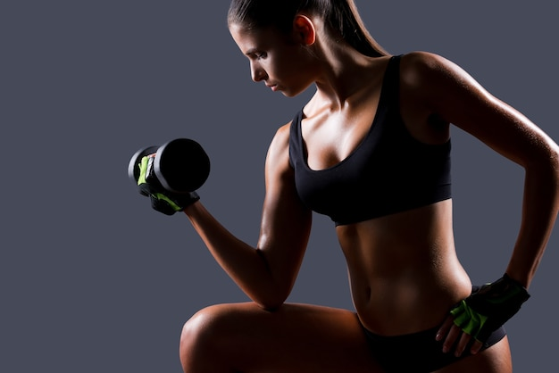 Stärkung ihrer muskeln. seitenansicht einer schönen jungen frau, die mit hanteln trainiert, während sie vor grauem hintergrund steht