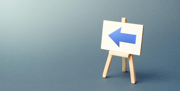 Staffelei mit einem blauen pfeil nach links. zeichen der richtung.