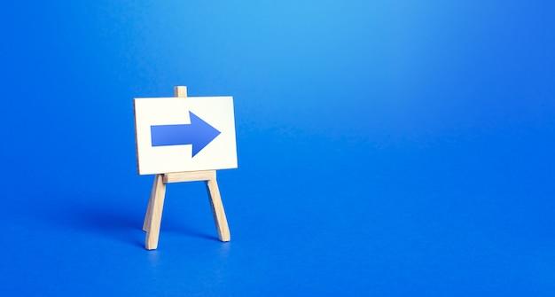 Staffelei mit einem blauen pfeil nach rechts. zeichen der richtung. werbung für den standort eines geschäfts oder einer verkaufsstelle