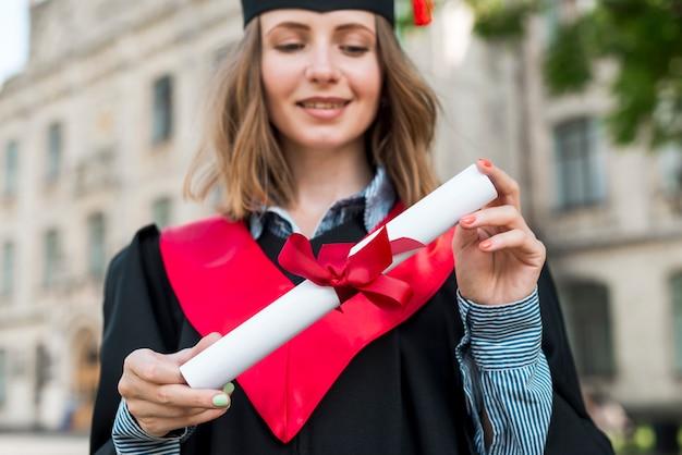 Staffelungskonzept mit dem mädchen, das ihr diplom hält