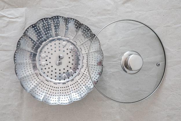 Stahldampfereinsatz für gesundes kochen, mit pfannendeckel, auf grauem papier.
