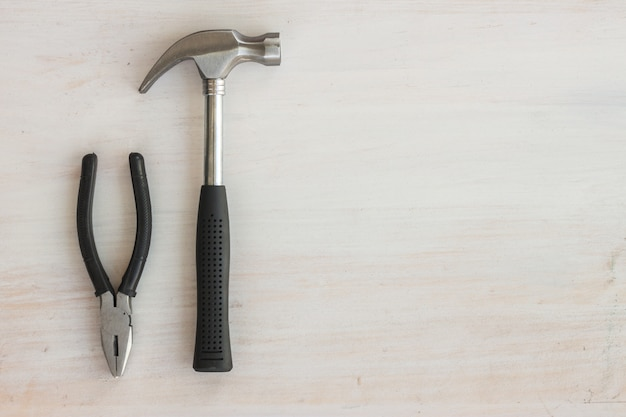Stahlhammer-schuttgriff und -zangen auf weißem holz