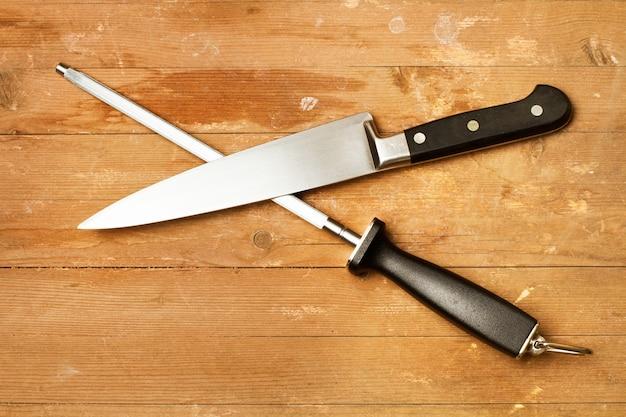 Stahlspitzer und ein küchenmesser auf einem rustikalen holztisch