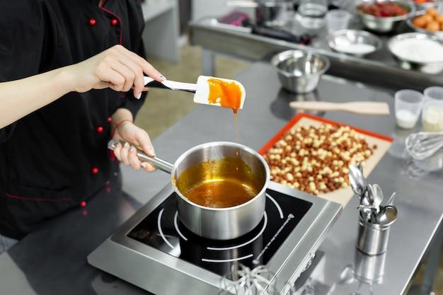 Stahltopf mit kochendem karamell zur herstellung von pralinen