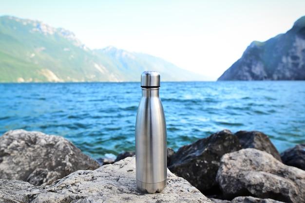 Stahlwasserflasche auf dem hintergrund des sees in den bergen riva del garda