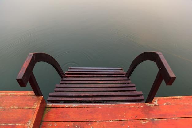 Stahlwassertreppe, ein treppenhaus, das zum wasser mit natürlichem wasseroberflächenhintergrund führt
