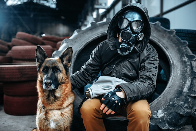 Stalker in gasmaske und hund, freunde in der postapokalyptischen welt. lebensstil nach der apokalypse auf ruinen, tag des jüngsten gerichts, tag des jüngsten gerichts