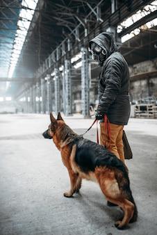 Stalker soldat in gasmaske und hund in verlassenem gebäude, überlebende nach dem atomkrieg. postapokalyptische welt. lebensstil nach der apokalypse auf ruinen, tag des jüngsten gerichts, tag des jüngsten gerichts