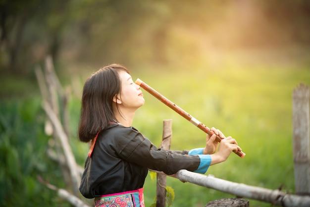 Stamm asiatische dame mädchen in benutzerdefinierten kleid hand halten flöte mit glücklichem gesicht in reisfeld in der monsunzeit gehen.