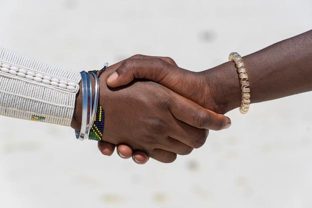Stammes-massai-männer, die händedruck im tropischen strand auf insel sansibar, tansania, afrika, nahaufnahme machen