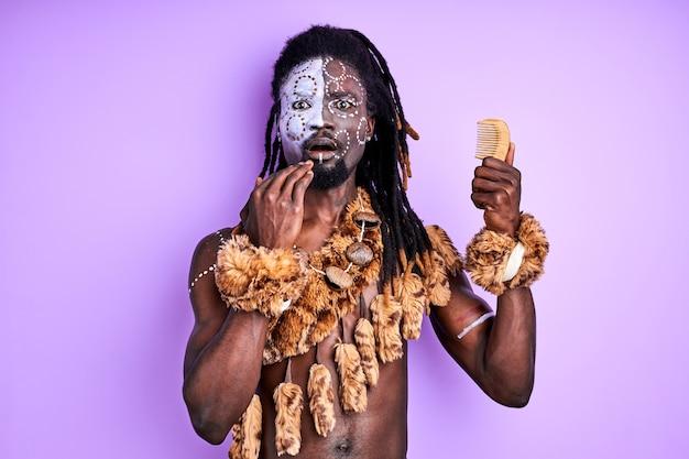 Stammes-primitiver mann sieht kamm an, er weiß nicht, wie man ihn benutzt, isoliert über lila wand
