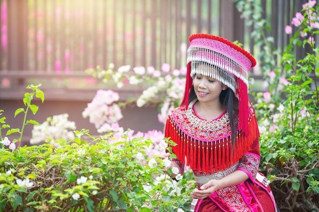 Stammes-schöne frau im roten traditionellen outfit im park