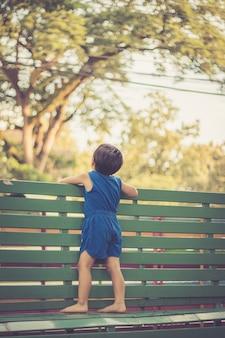 Stand des kleinen jungen auf dem grünen stuhl, der sonnenunterganghimmel betrachtet