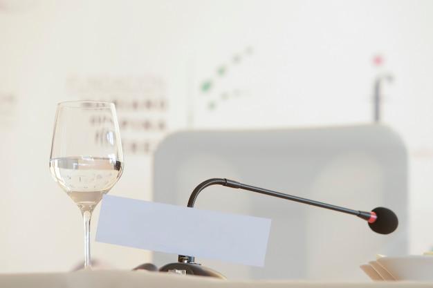 Stand mit stuhl für pressekonferenz mit mikrofon und wasserglas