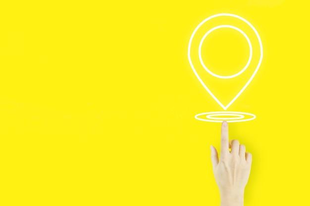 Standortkonzept für pin-adressen. hand der jungen frau zeigt mit hologramm location marker auf gelbem hintergrund. konzept der internetkarten und navigation.