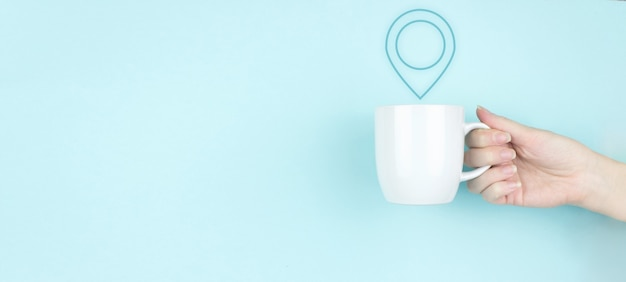 Standortkonzept für pin-adressen. mädchen hand halten kaffeetasse am morgen mit zeichen location marker icon auf blauem hintergrund. konzept der internetkarten und navigation.