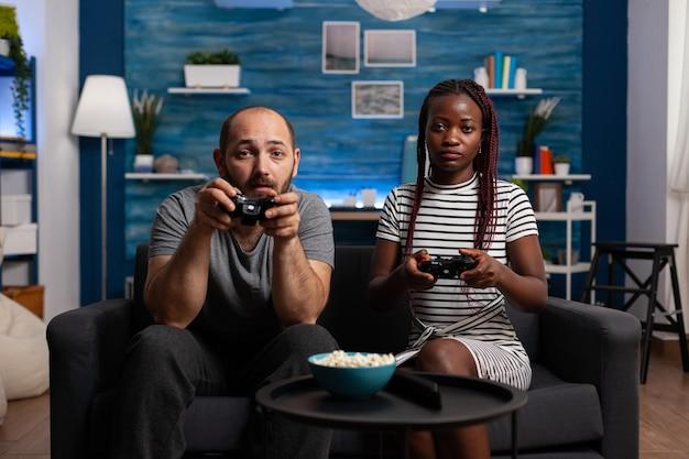 Standpunkt eines interracial paares, das ein videospiel auf der konsole spielt